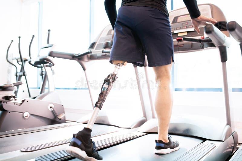 Homem muscular deficiente que corre na escada rolante fotos de stock