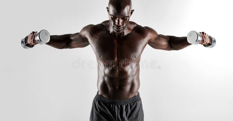 Homem muscular descamisado que exercita com pesos da mão imagens de stock