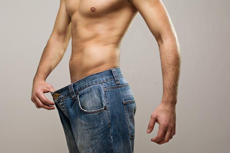 Homem muscular do ajuste que veste calças de brim grandes após a dieta