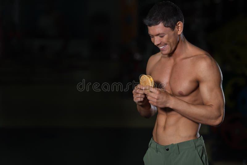 Homem muscular do conceito insalubre do alimento com Hamburger fotografia de stock royalty free