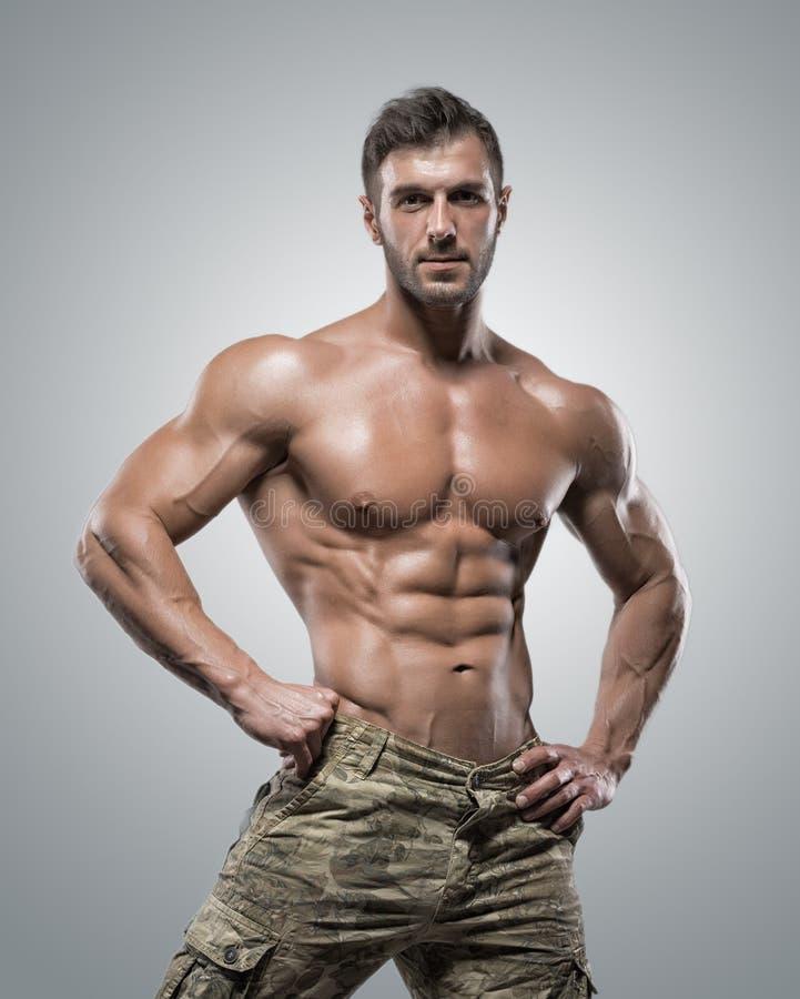 Homem muscular do halterofilista do atleta em um fundo cinzento imagens de stock