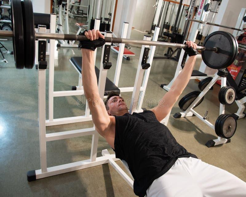 Homem muscular do halterofilista durante a imprensa de banco foto de stock royalty free