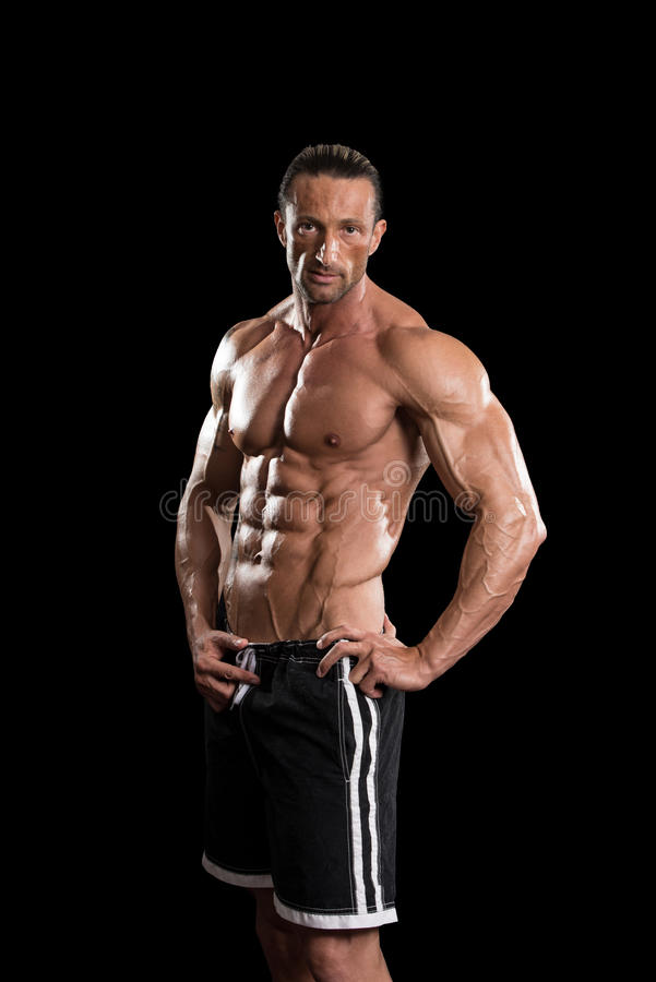 Homem muscular do halterofilista que levanta sobre o fundo preto fotos de stock royalty free