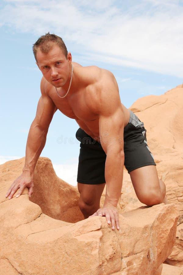 Homem muscular em rochas vermelhas fotos de stock