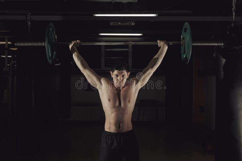 Homem muscular em um gym do crossfit que levanta um barbell fotografia de stock
