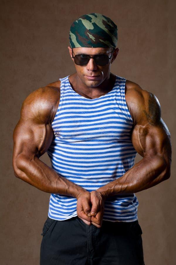 Homem muscular em uma camisa listrada. foto de stock