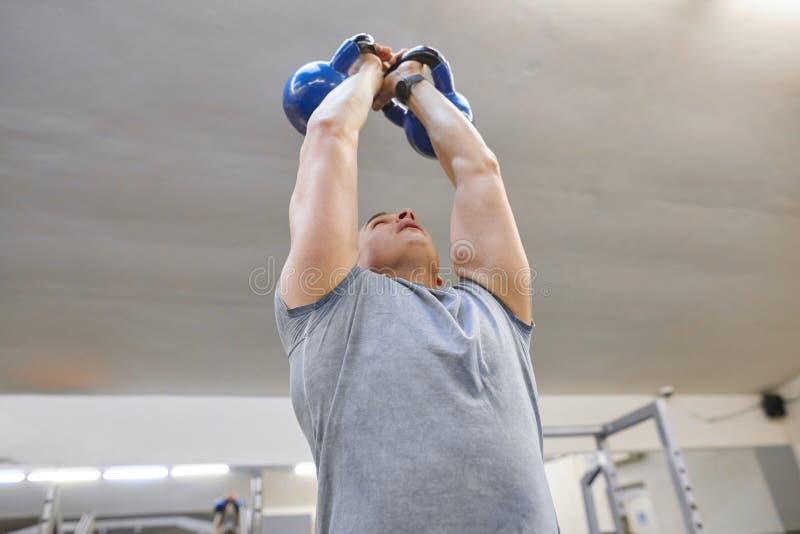 Homem muscular forte do atleta que exercita com kettlebells no gym, treinamento do peso fotografia de stock royalty free
