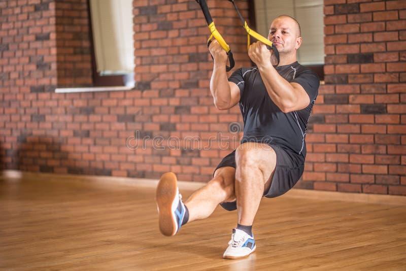 Homem muscular forte que exercita com facilidades do trx no gym ou no wor imagem de stock royalty free