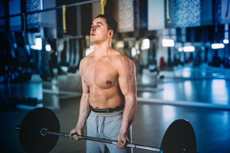 Homem muscular, instrutor da aptidão que dá certo no gym e que faz exercices do bíceps fotografia de stock
