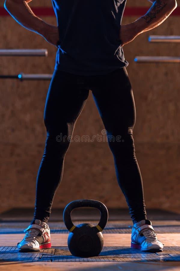 Homem muscular masculino que faz o exercício do kettlebell no gym imagem de stock royalty free