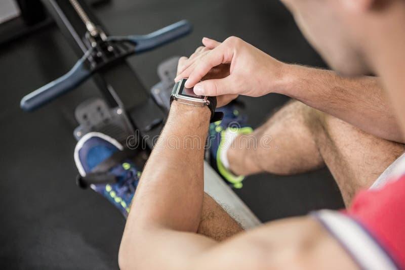 Homem muscular na máquina de enfileiramento usando o relógio esperto imagens de stock royalty free
