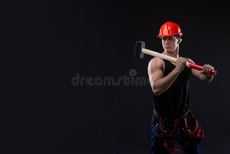 Homem muscular no capacete alaranjado com a grande anatomia que levanta em um fundo preto com um hummer grande em suas mãos foto de stock royalty free