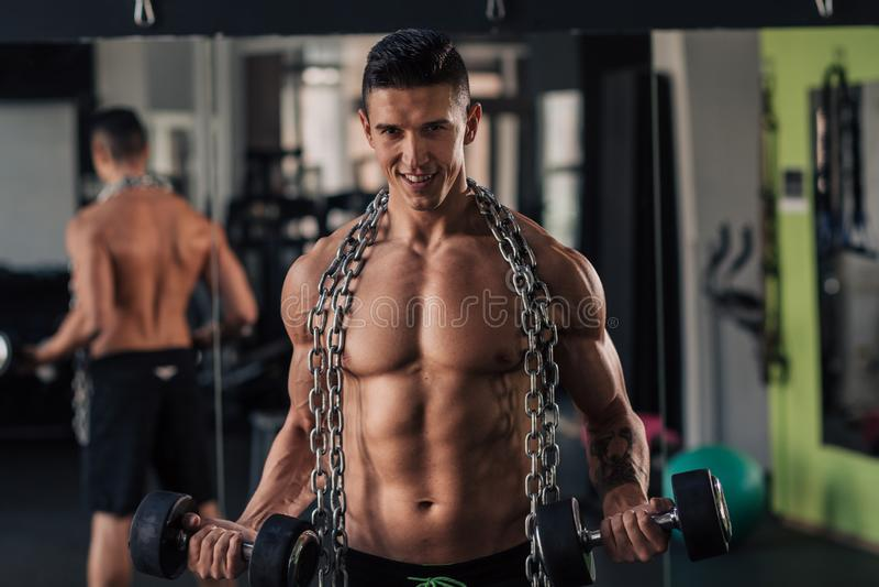 Homem muscular novo no gym que faz o exerc?cio fotografia de stock royalty free