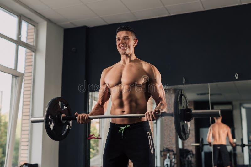 Homem muscular novo no gym que faz o exerc?cio imagem de stock