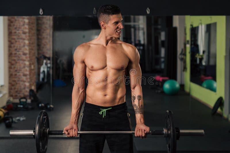 Homem muscular novo no gym que faz o exerc?cio fotos de stock