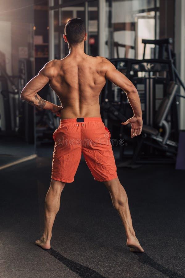 Homem muscular novo no gym que faz o exerc?cio foto de stock