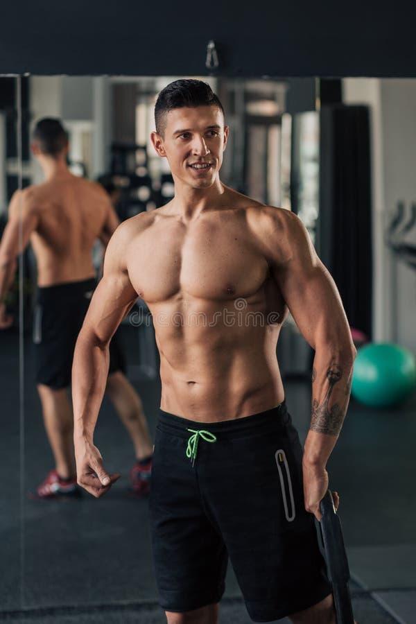 Homem muscular novo no gym que faz o exerc?cio imagens de stock