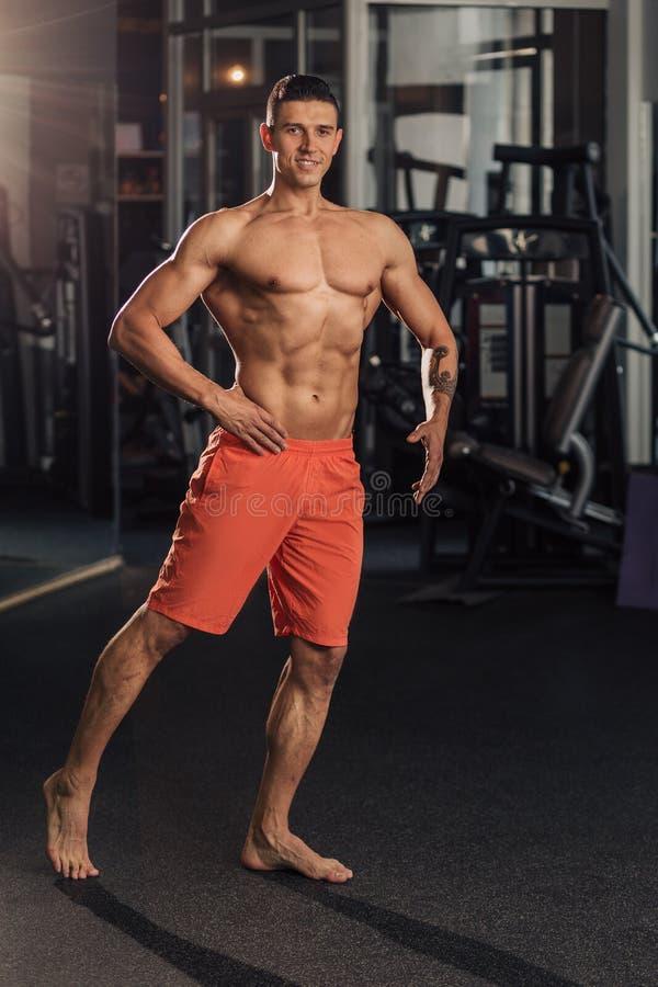 Homem muscular novo no gym que faz o exerc?cio foto de stock royalty free