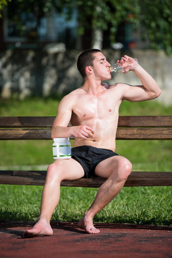 Homem muscular novo que bebe uma garrafa de água imagens de stock