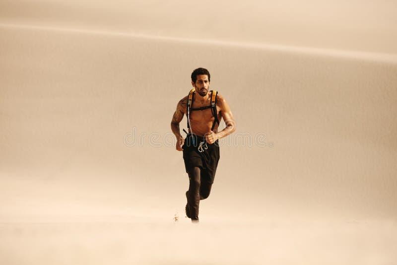 Homem muscular que corre em dunas de areia imagens de stock
