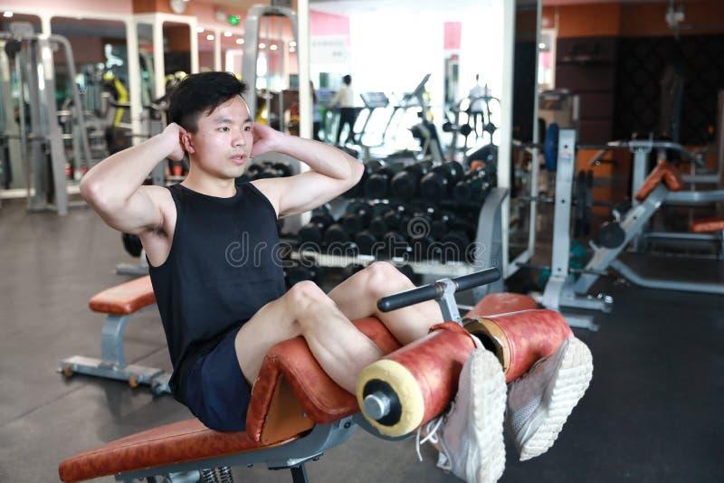 Homem muscular que dá certo no gym Homem que faz triturações do situp foto de stock