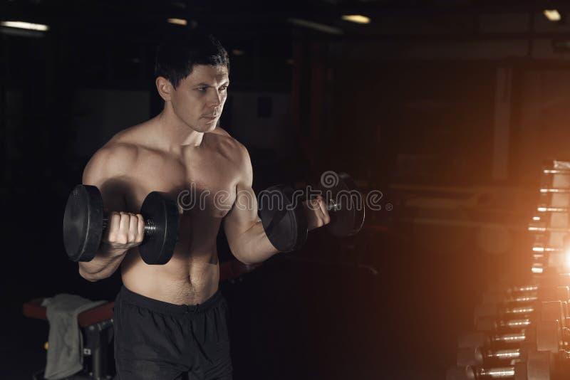 Homem muscular que dá certo no gym que faz exercícios com pesos a fotos de stock