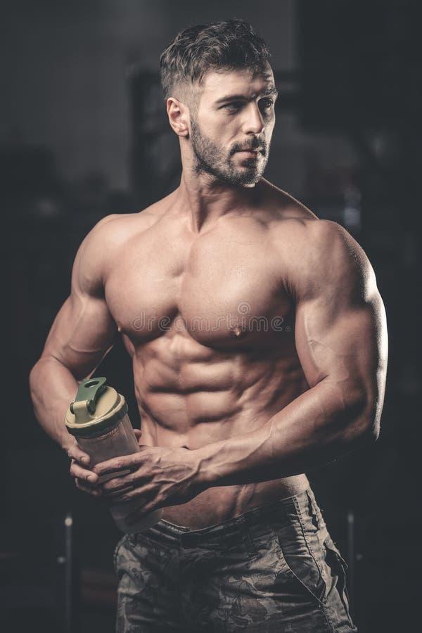 Homem muscular que descansa após o exercício e que bebe do abanador fotografia de stock royalty free