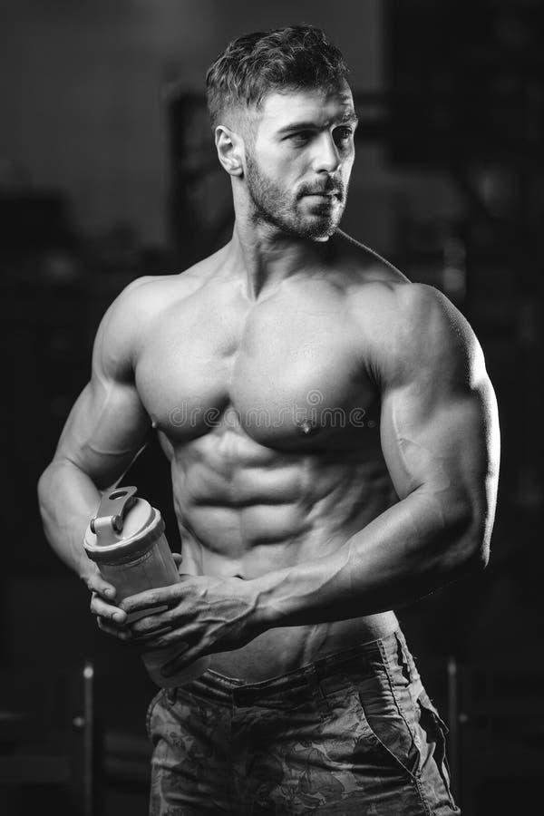 Homem muscular que descansa após o exercício e que bebe do abanador imagens de stock