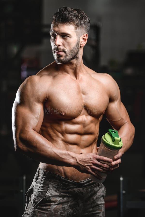 Homem muscular que descansa após o exercício e que bebe do abanador imagem de stock royalty free