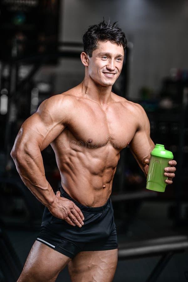 Homem muscular que descansa após o exercício e que bebe do abanador fotografia de stock