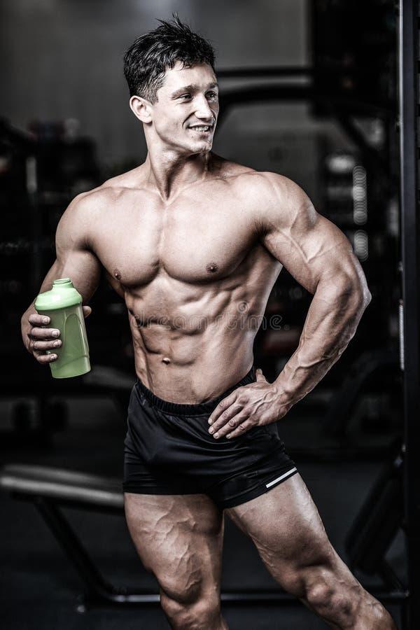 Homem muscular que descansa após o exercício e que bebe do abanador fotos de stock
