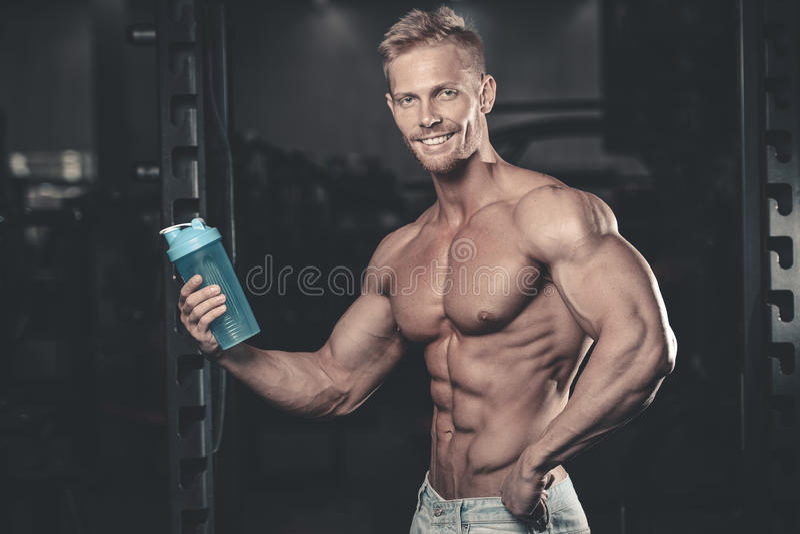 Homem muscular que descansa após o exercício e que bebe do abanador imagens de stock royalty free