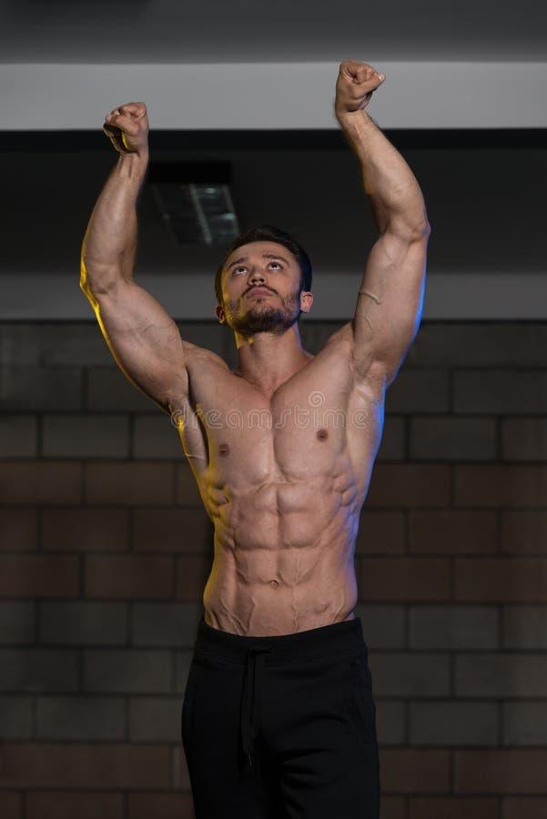 Homem muscular que dobra os músculos no gym fotografia de stock royalty free