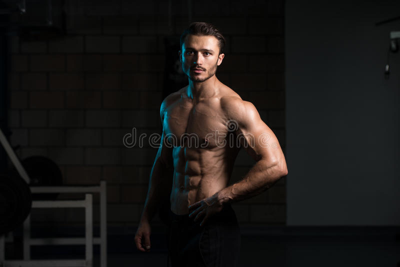 Homem muscular que dobra os músculos no gym imagens de stock