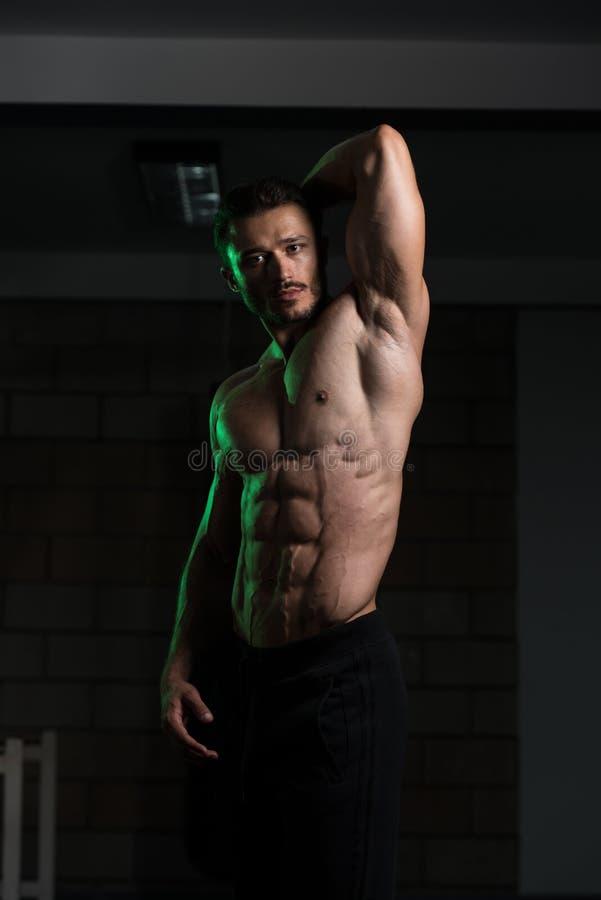 Homem muscular que dobra os músculos no gym fotos de stock royalty free