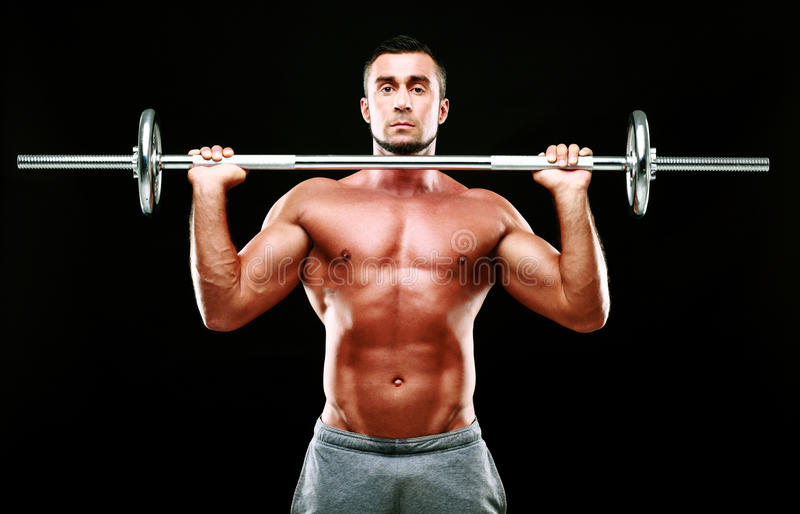 Homem muscular que elabora com barbell fotografia de stock royalty free
