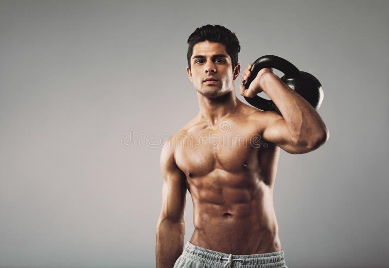 Homem muscular que executa o exercício do crossfit com o kettlebell foto de stock
