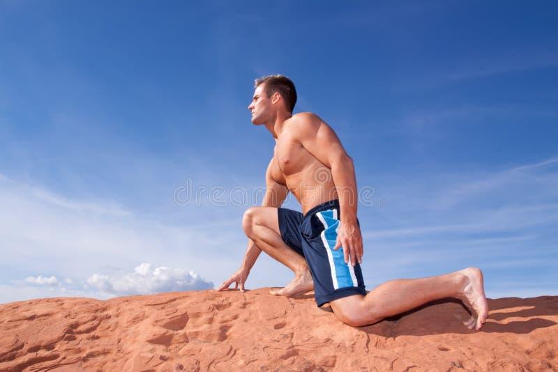 Homem muscular que exercita em rochas vermelhas foto de stock