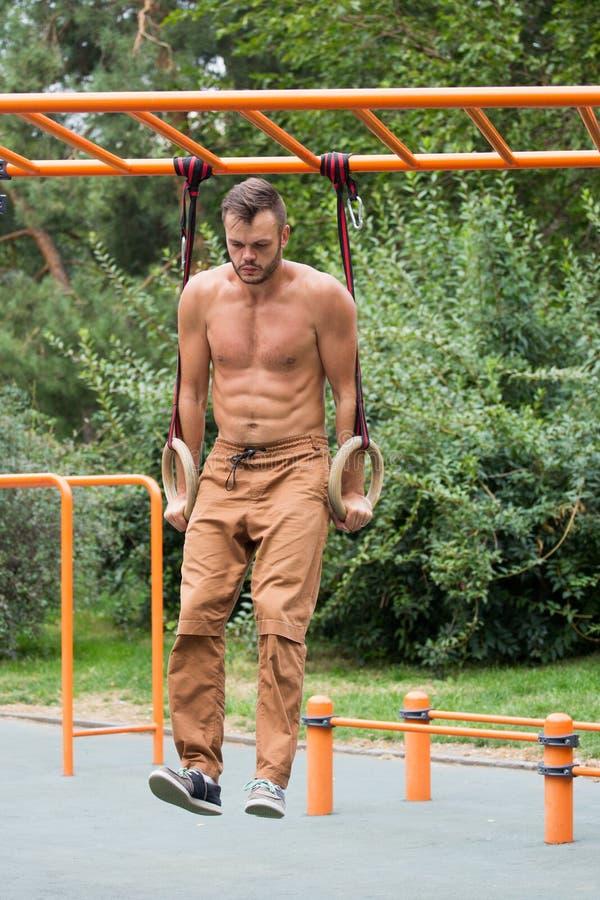 Homem muscular que exercita no anel ginástico exterior fotos de stock