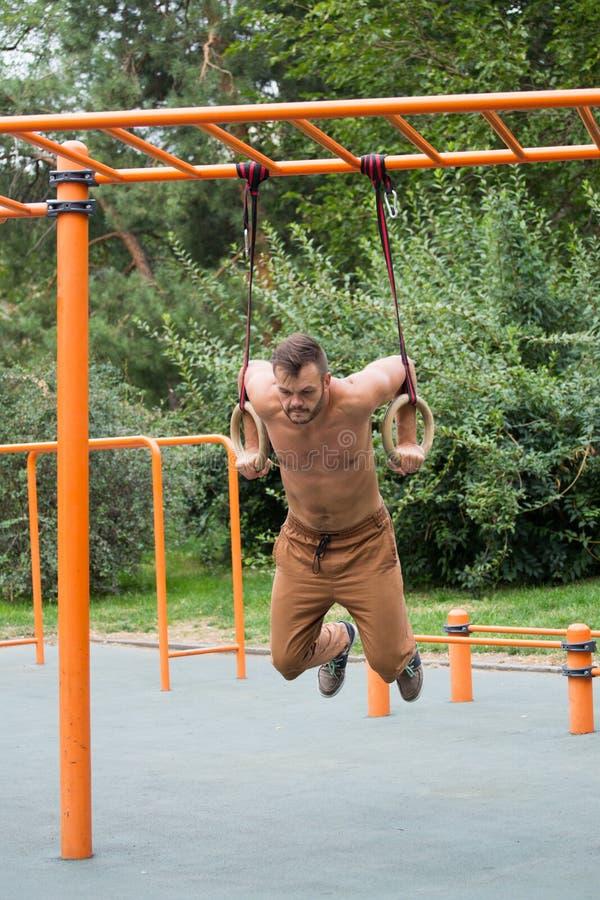 Homem muscular que exercita no anel ginástico exterior fotos de stock royalty free