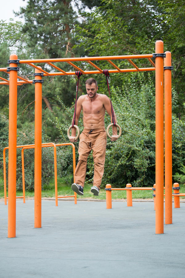Homem muscular que exercita no anel ginástico exterior foto de stock royalty free