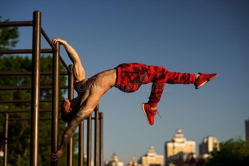 Homem muscular que faz a bandeira na rua Exercício da rua imagem de stock