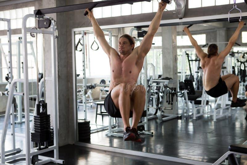 Homem muscular que faz levantar na barra e o bombeamento acima de seis blocos abdominais no gym exercício, exercícios, treinament foto de stock