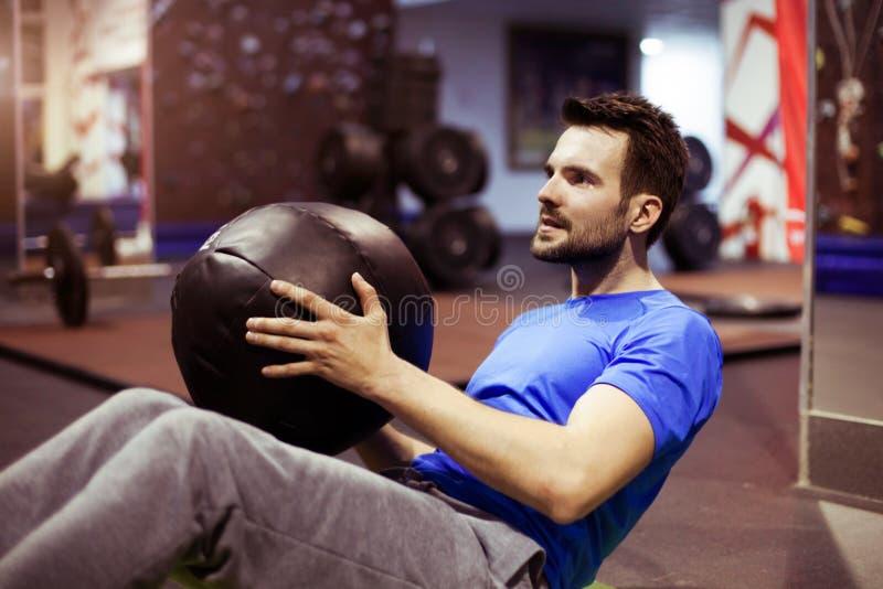 Homem muscular que faz o exercício com a bola de medicina no gym do crossfit fotografia de stock