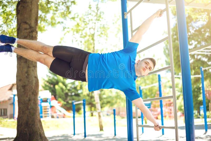 Homem muscular que faz o exercício humano da bandeira imagem de stock royalty free