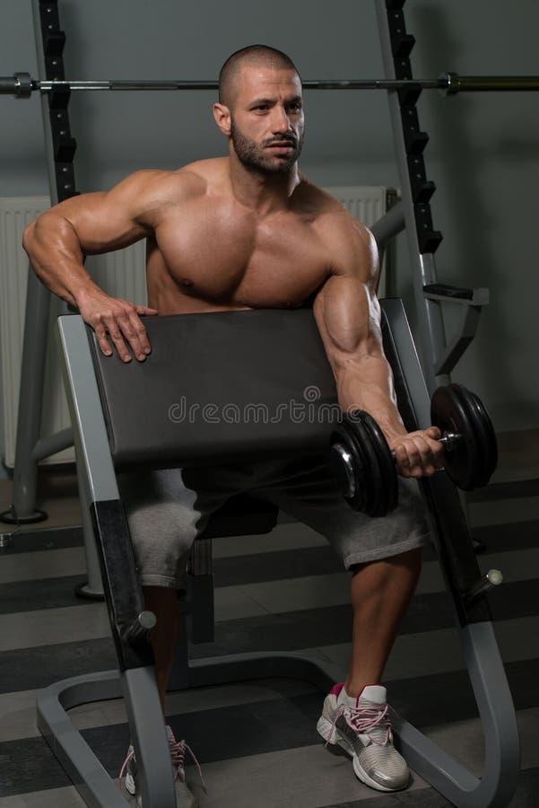 Homem muscular que faz o exercício pesado para o bíceps foto de stock