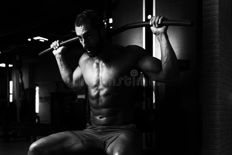 Homem muscular que faz o exercício pesado para a parte traseira imagens de stock royalty free
