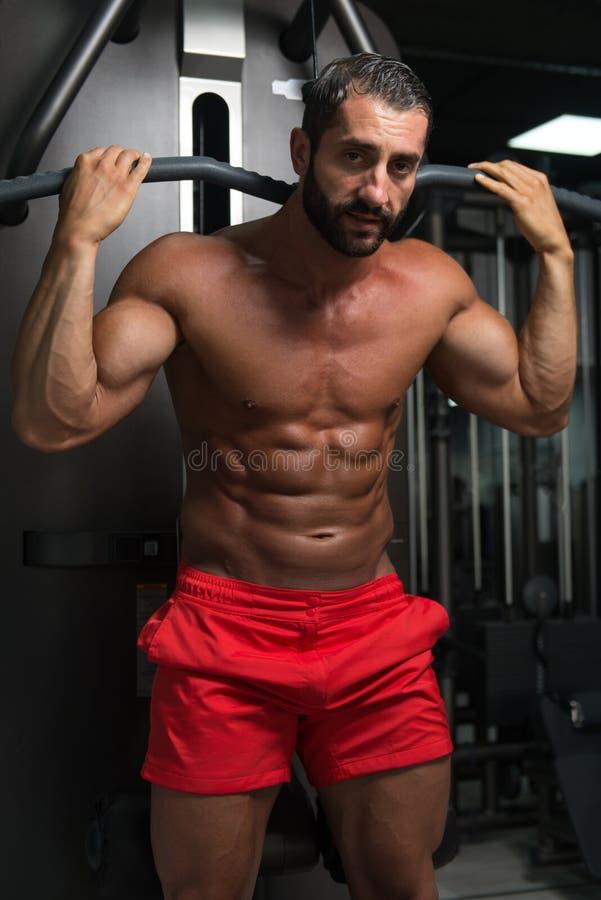 Homem muscular que faz o exercício pesado para a parte traseira fotografia de stock royalty free
