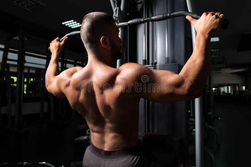 Homem muscular que faz o exerc?cio pesado para a parte traseira imagem de stock