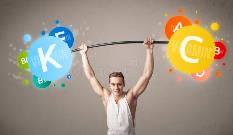 Homem muscular que levanta pesos coloridos da vitamina foto de stock